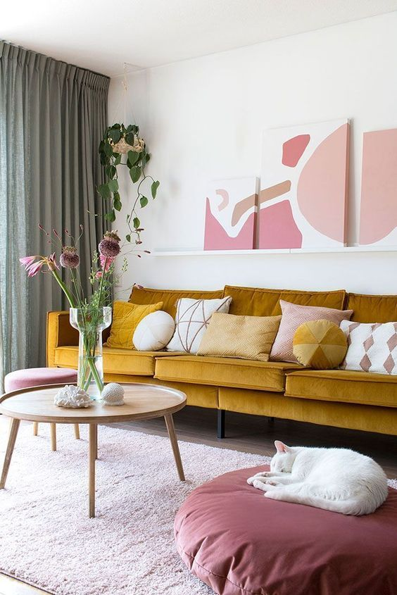 a refined living room with a mustard sofa, a ledge gallery wall, touches of pink and mauve for a very elegant and chic look