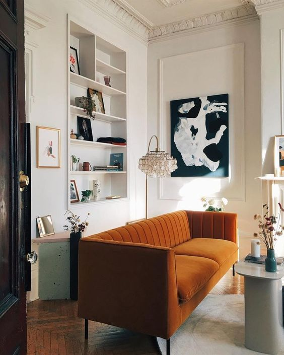 a refined living room with a niche with built-in shelves, a rust-colored sofa, a black and white artwork and dried blooms