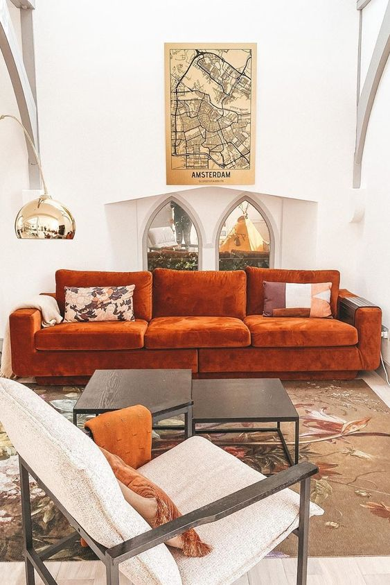 a refined living room with a rust-colored sofa, a duo of tables, a creamy chair, a polished floor lamp is amazing