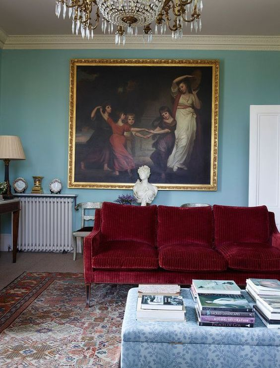 a refined living room with blue walls, a deep red sofa, a floral ottoman, a bold vintage artwork and a crystal chandelier