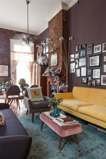 a refined mid-century modern living room with brown walls, a yellow sofa, a grey one and pretty furniture, a gallery wall