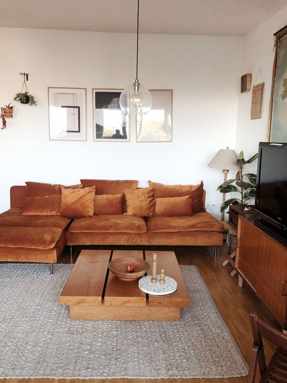a refined modern living room with 70s vibs, a rust colored IKEA sofa, wooden furniture and potted plants plus artworks
