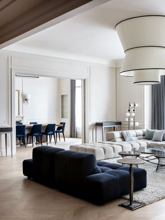 a refined modern living room with a creamy and navy low sofa, statement lamps and small round coffee tables