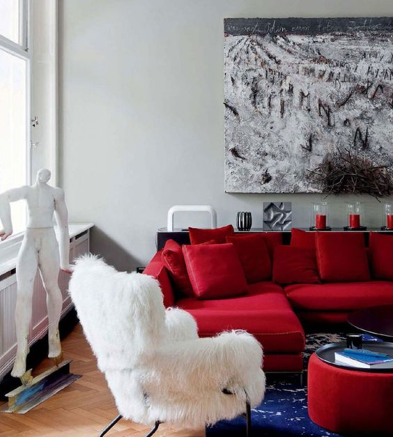 a refined modern living room with a hot red sectional, a white faux fur chair, a bold red ottoman and a creative artwork