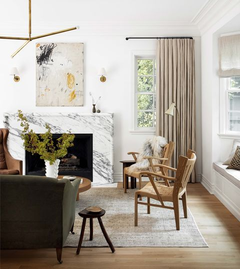 a refined neutral living room with a whiet stone clad fireplace, an artwork, blonde wood and leather chairs, a green sofa and touches of gold