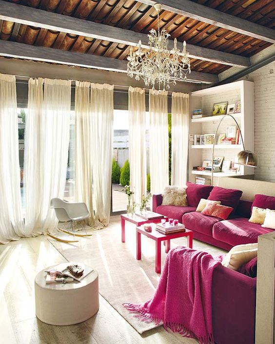 a refined neutral living room with built-in shelves, two fuchsia sofas, neutral furniture and textiles plus a crystal chandelier