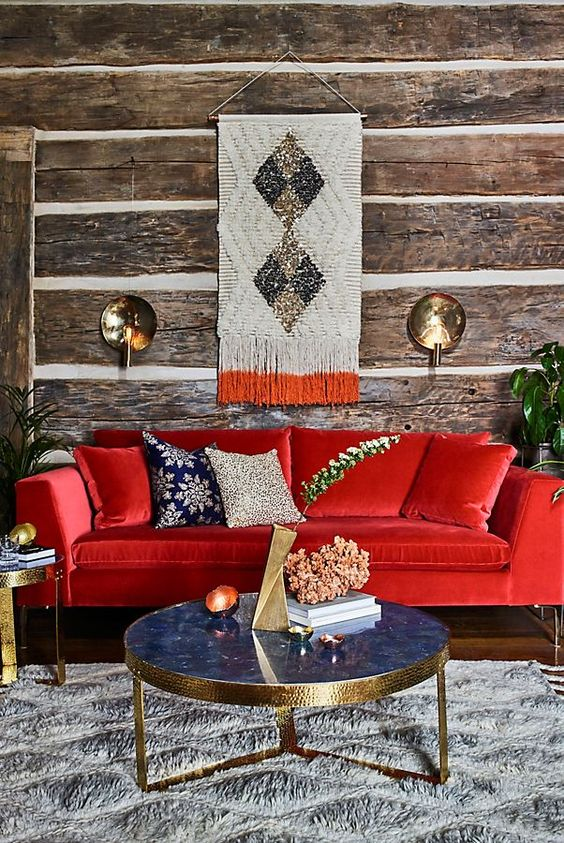 a rustic living room with wood wallpaper walls, a bold red sofa, a refined blue marble table and touches of gold here and there