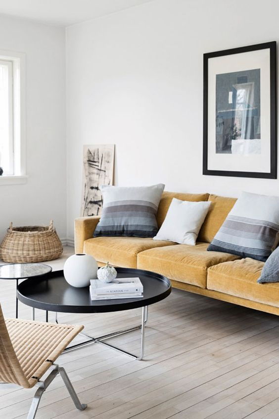 a serene Scandinavian living room with a light yellow sofa, striped pillows, round tables and a rattan lounger is wow