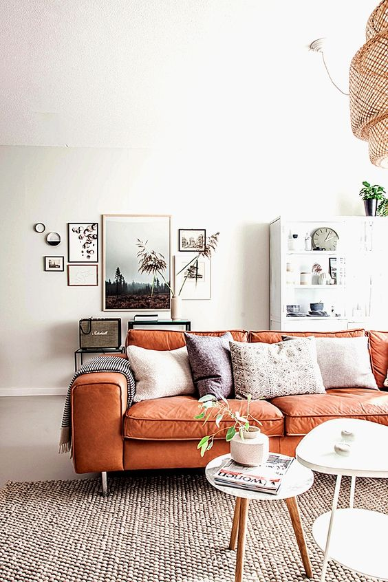 a serene Scandinavian living room with neutral furniture, a chic gallery wall and an orange leather sofa with boho pillows is amazing