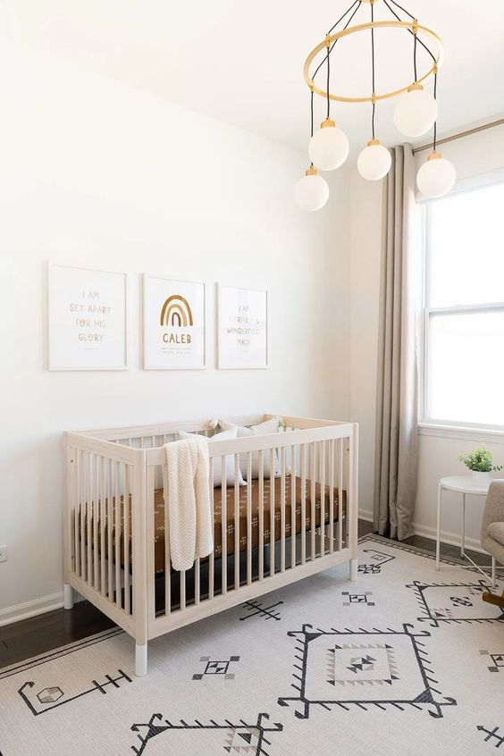 a serene and neutral nursery with a printed rug, grey curtains, a neutral crib and a pretty gallery wall plus a chandelier with hanging bulbs