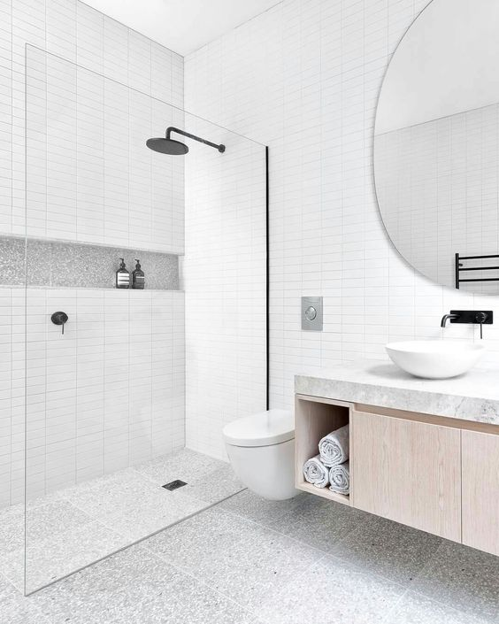 a serene bathroom clad with skinny white tiles, grey terrazzo ones on the floor and a floating vanity and a round mirror