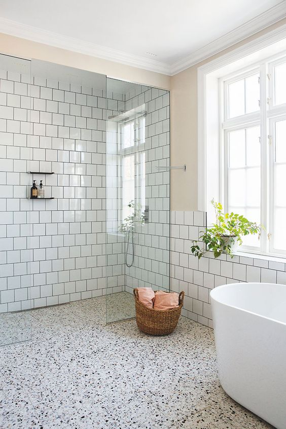 a serene bathroom with white square tiles, a white terrazzo floor for more interest and a white oval bathtub