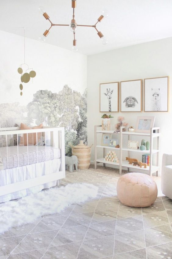 a serene neutral nursery with a forest wall mural, a large crib, a storage unit, a gallery wall with art and some layered rugs