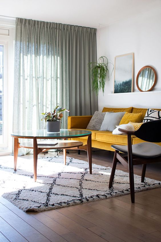 a simple and cool mid century modern living room with a yellow sofa, graphic pillows, a modern chair and table plus green curtains