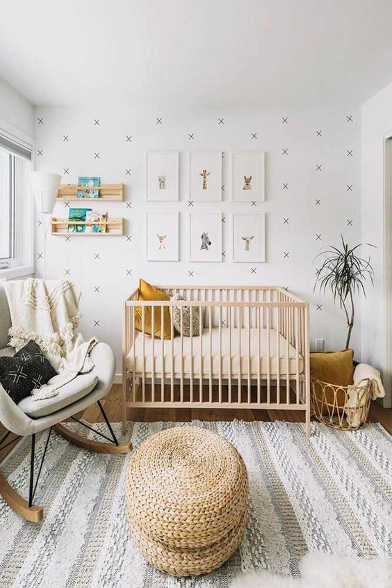 a simple modern nursery with an accent wall, a light stained crib, a grey rocker, a rattan basket and some shelves for books