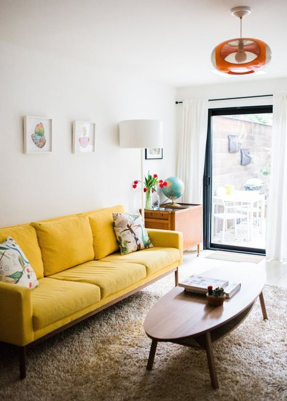 a small and cheerful living room with a yellow sofa, a low oval table, a small gallery wall and a bright lamp