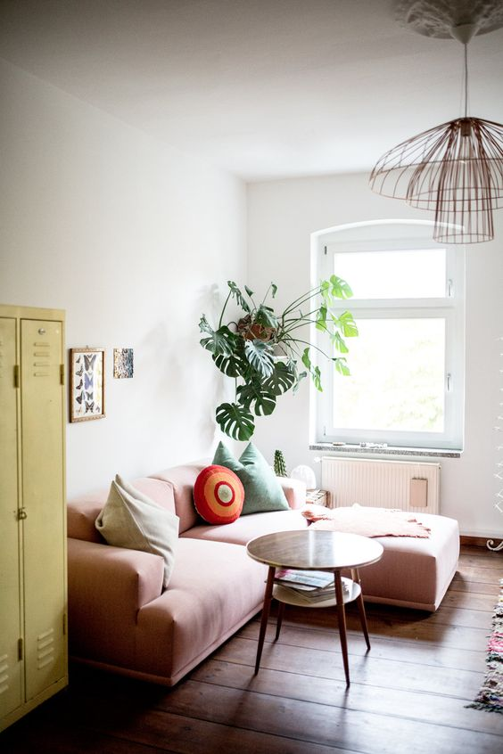 a small bright living room with a yellow locker, a low pink sofa, some potted plants and a catchy pendant lamp