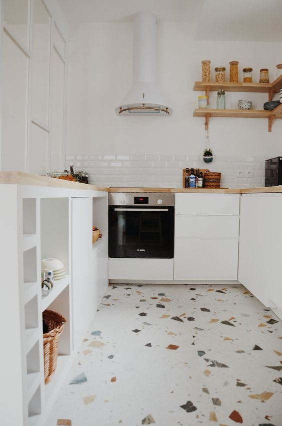 a small neutral kitchen with sleek cabinets and butcherblock countertops, a white hood and a fun terrazzo floor that brings a playful feel here