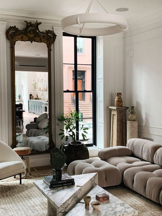 a sophisticated living room with a grey low sofa, marble tables, a large mirror in a refined frame and a potted plant