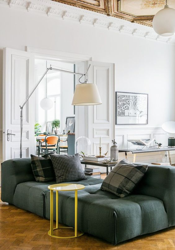 a sophisticated living room with a low green sofa, a yellow table, cool lamps and various coffee tables and an artwork