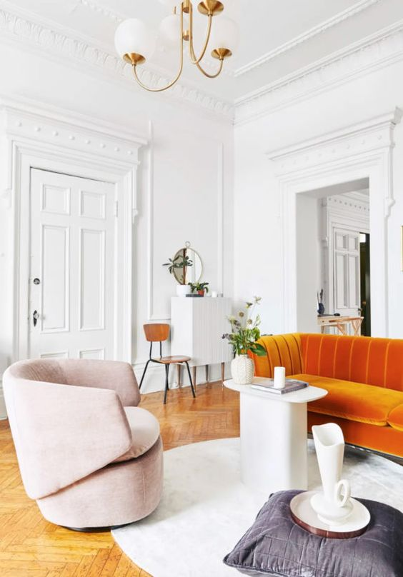 a sophisticated living room with an orange sofa, a pink chair, a quirky table and a pillow plus a jug is a catchy space