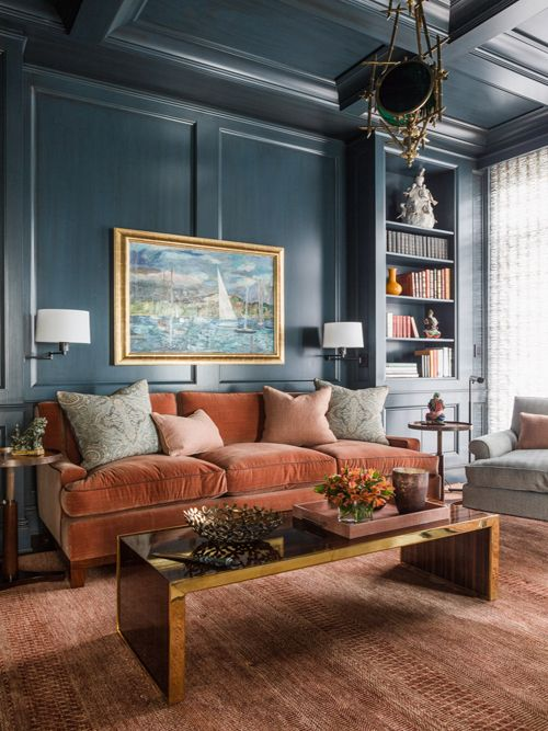 a sophisticated living room with navy walls, a rust colored velvet sofa, a low polished table, built in shelves
