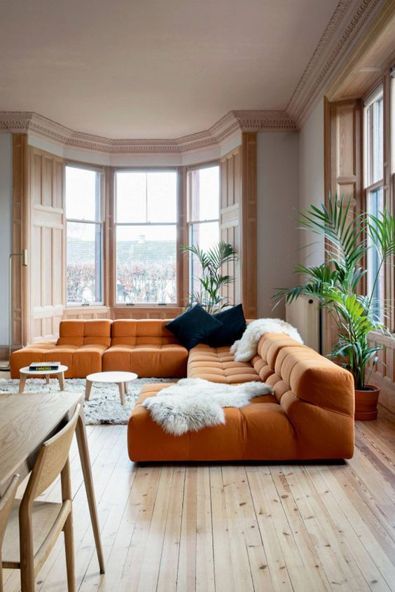 a spacious living room with a low orange sofa, faux fur, navy pillows and gorgeous light stained windows