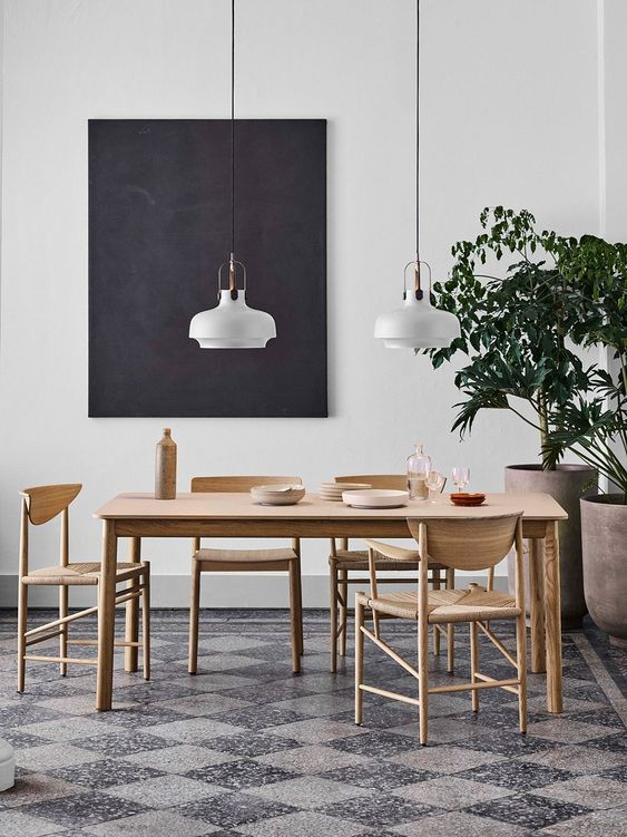 a stylish Scandinavian dining room with a blonde wood dining set, a tiled floor, pendant lamps and a black artwork