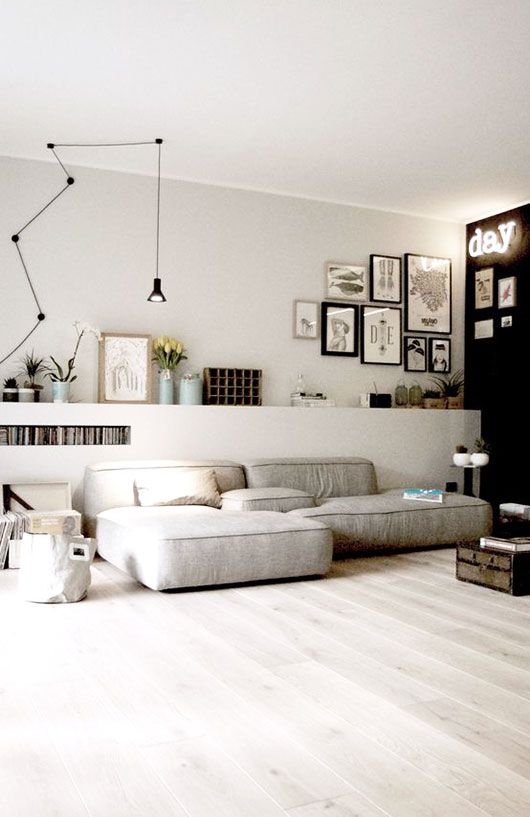 a stylish contemporary living room with a black accent wall, a low grey sofa, a raised shelf with potted plants and a gallery wall