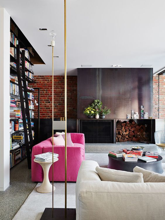 a stylish contemporary living room with a metal fireplace and firewood storage, a hot pink sofa, a neutral one, a large bookcase and gold touches