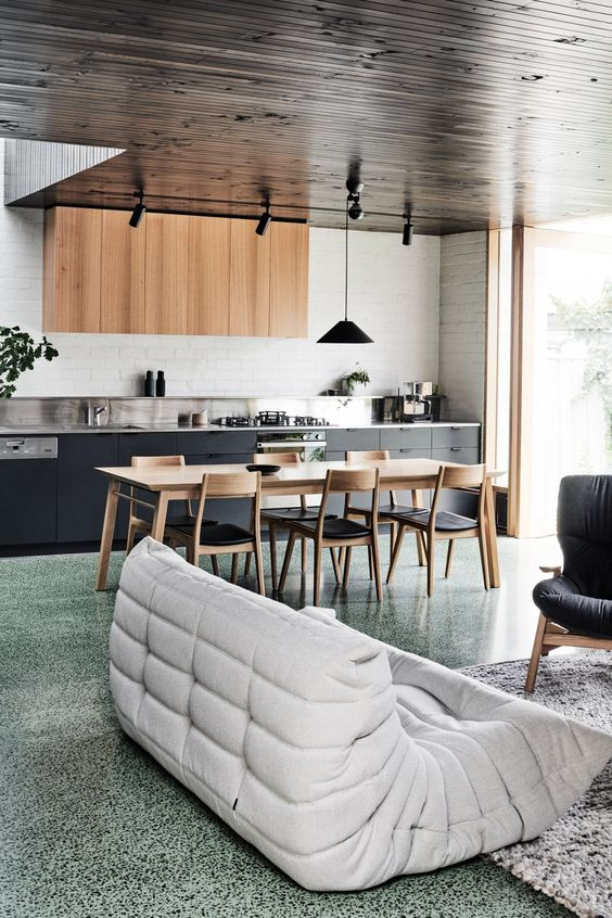 a stylish contemporary space with black and stained cabinetry, a green terrazzo floor and comfortable furniture