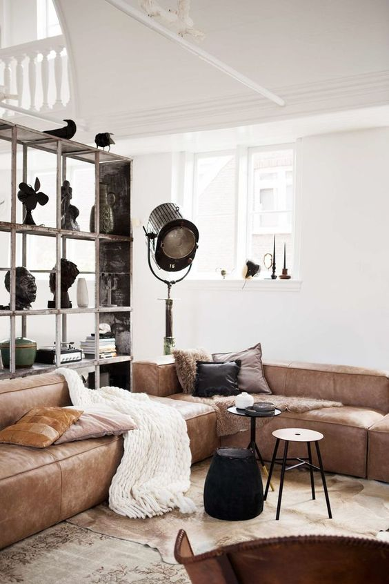 a stylish living room with a brown low sofa, small side tables, a large storage unit and some lamps