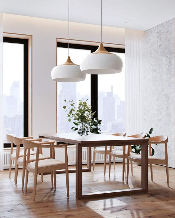 a stylish mid-century modern dining room with a dining table and blonde wood chairs with neutral seats plus elegant pendant lamps