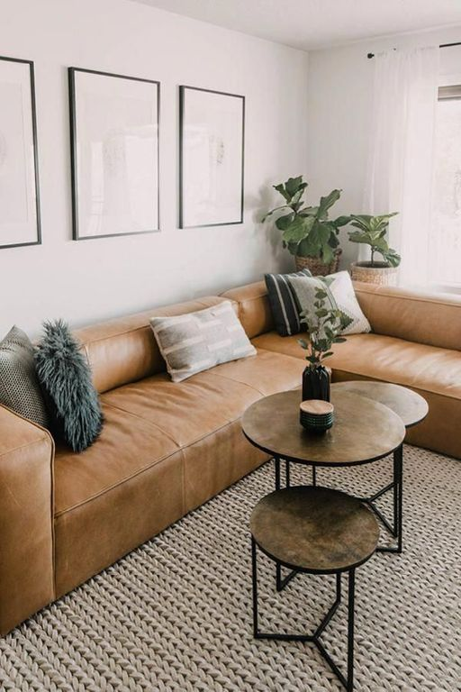 a stylish modern living room with a low brown leather sofa, several round tables, a gallery wall and potted plants