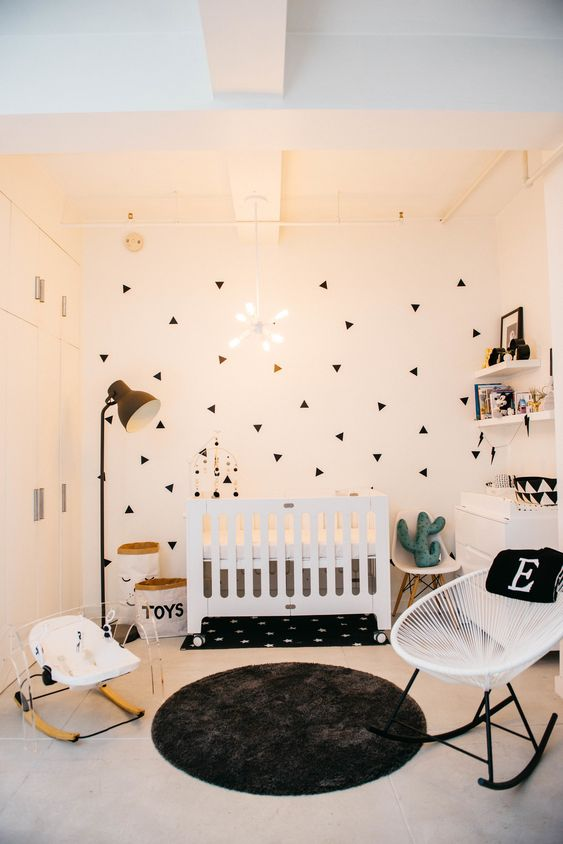 a stylish modern nursery with a geo print wall, white furniture, a floor lamp, floating shelves and a cool modenr chandelier
