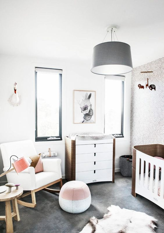 a stylish modern nursery with black framed windows, a grey chandelier, a white rocker and white and stained furniture, a colro block pouf and layered rugs