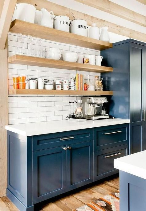 a stylish navy farmhouse kitchen with blonde wood beams and shelves, white countertops and white skinny tiles