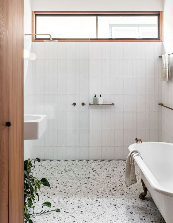 a stylish neutral bathroom with white skinny tiles, a white terrazzo floor, a vintage tub and a white wall mounted sink