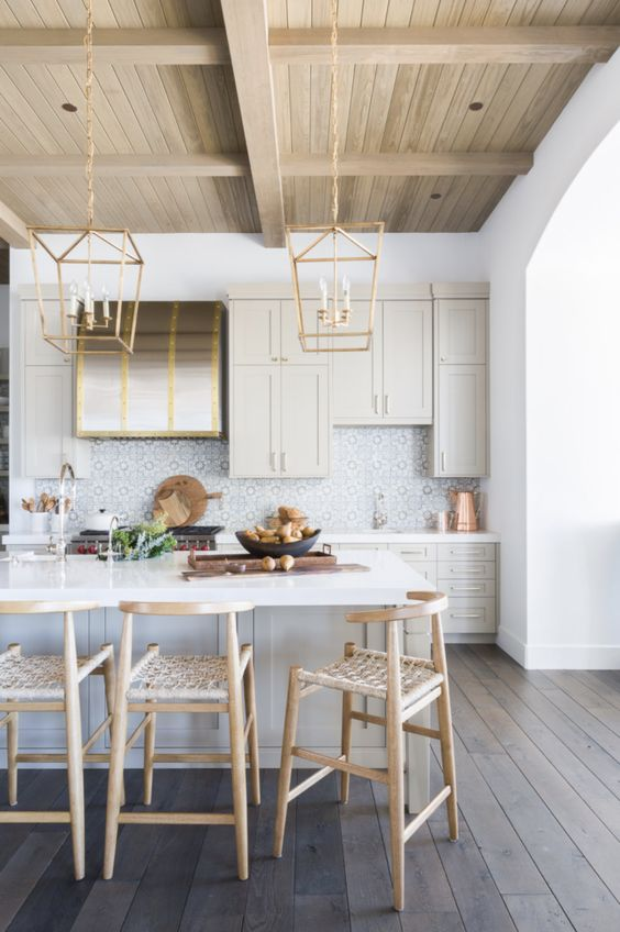 a very chic kitchen in light grey, with a blonde wood ceiling and tall stools with woven seats, gold pendant lamps