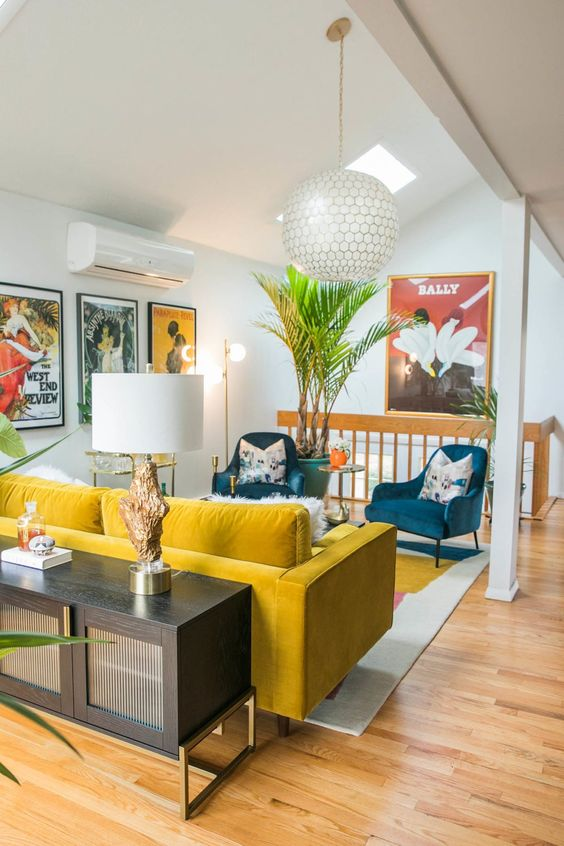 a vibrant mid-century modern space with a yellow sofa and blue chairs, floral pillows, potted plants and a credenza with a lamp