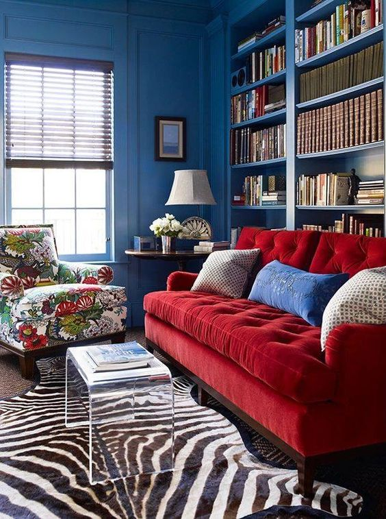 a vibrant space with blue walls, built in bookshelves, a red sofa and a floral chair, layered rugs and an acrylic table