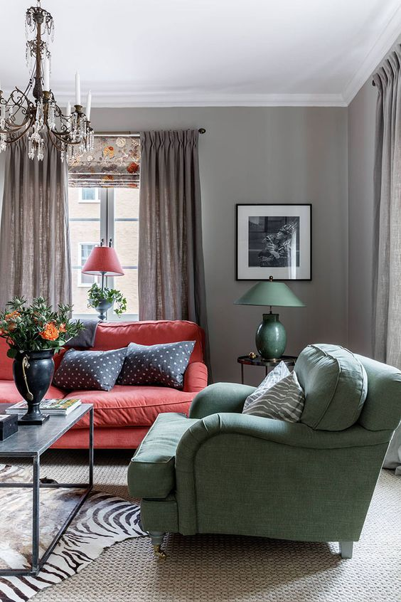 a vintage Scandi-inspired interior with grey walls, a red sofa, a green chair and a vintage crystal chandelier