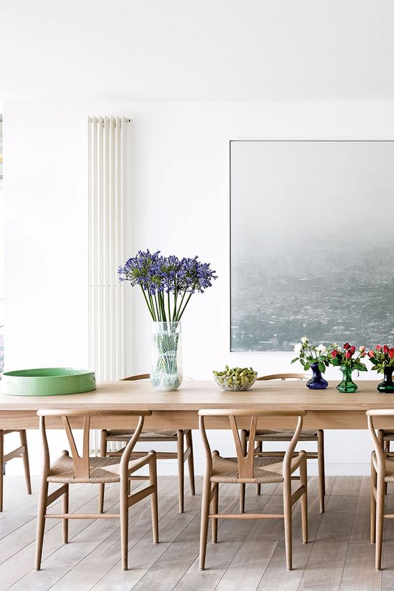 a vivacious dining room with blonde wood furniture, a beautiful artwork on the wall, blooms and greenery