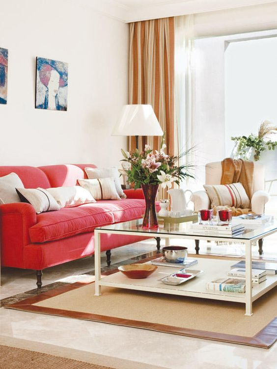 a vivacious living room with a red sofa, neutral furniture, a cool lamp, a lovely gallery wall and striped curtains