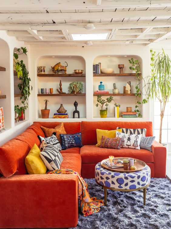a vivacious living room with niches with built-in shelves, an orange sofa, bold textiles and potted plants for a maximalist feel