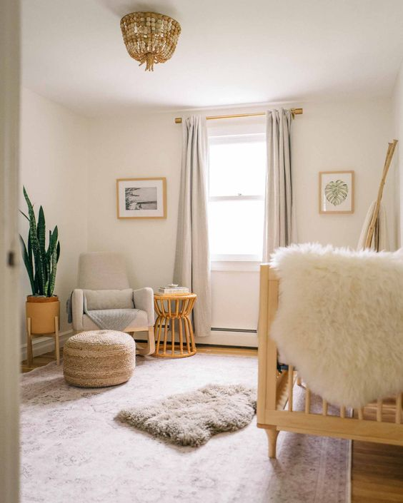a warm and welcoming neutral nursery with a large wooden crib, a neutral chair, a stool or a side table, a potted plant and a wooden bead  chandelier