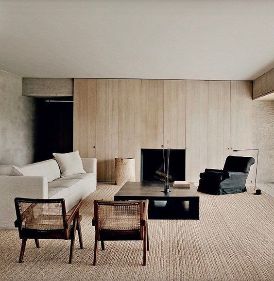 a warm neutral contemporary living room with a blonde wood wall, a fireplace, chic furniture and a large carpet