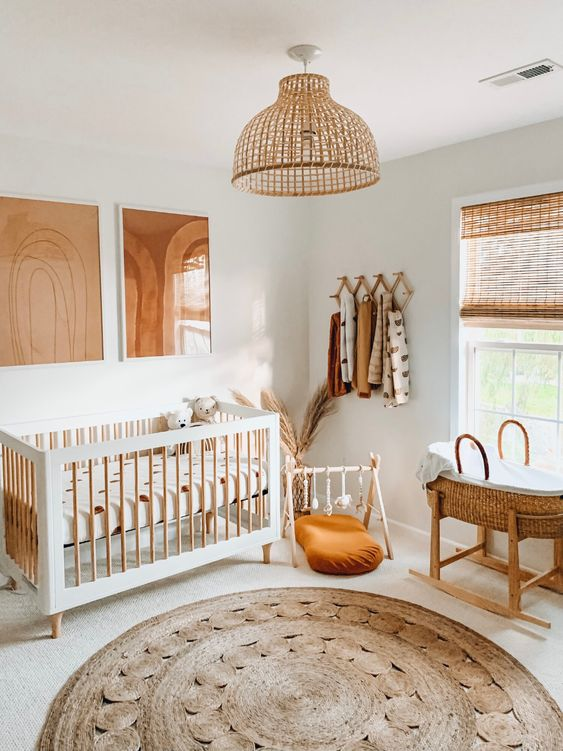 a warm neutral nursery with a cool crib, a baby cot, a jute rug, some artworks, shutters and a rattan lamp over the space