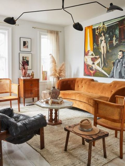 a welcoming 70s inspired living room with a rust-colored sofa, rattan, wooden and leather furniture, a black chandelier and a statement artwork