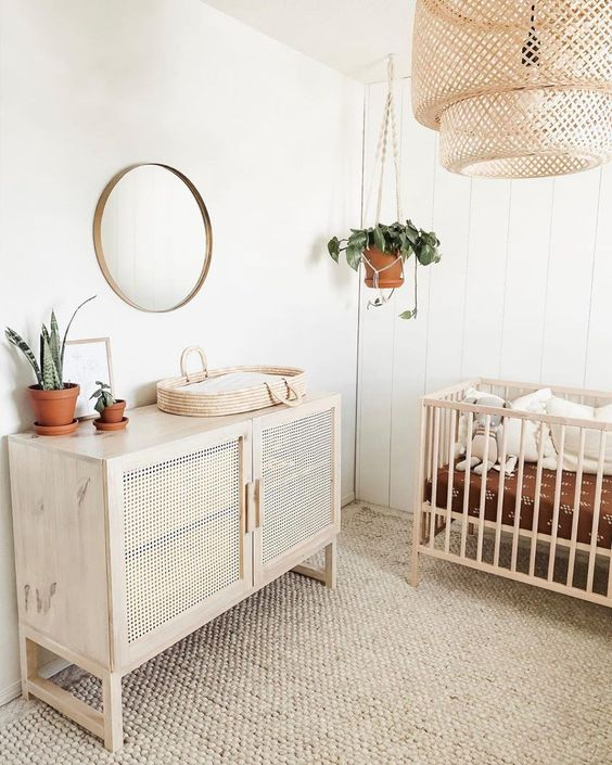 a welcoming neutral nursery with a jute rug, a crib, a rattan credenza, a woven lamp and a round mirror plus potted plants